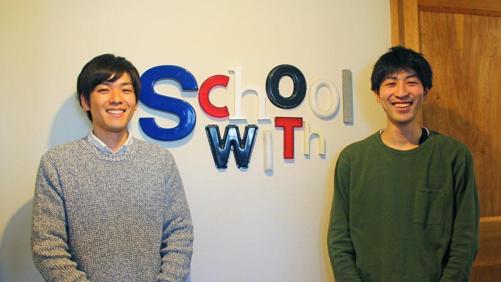 写真:ロゴを背景に立っているお二人