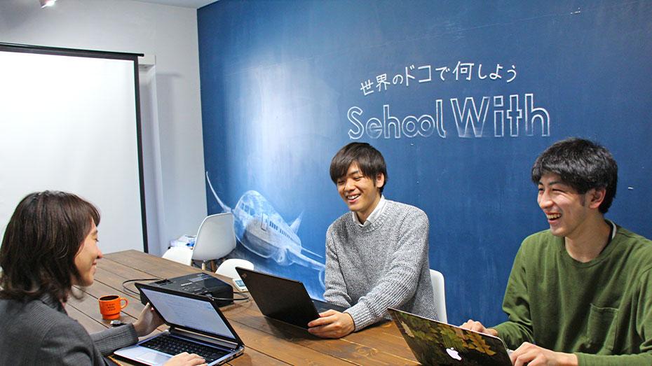 写真:笑顔でインタビューに答えるお二人、部屋の壁にはチョークでロゴが書かれている